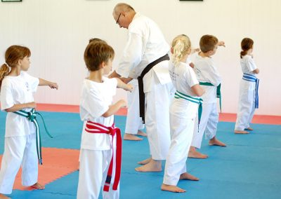 Sempai Vesa correcting technique as the children practice their kata